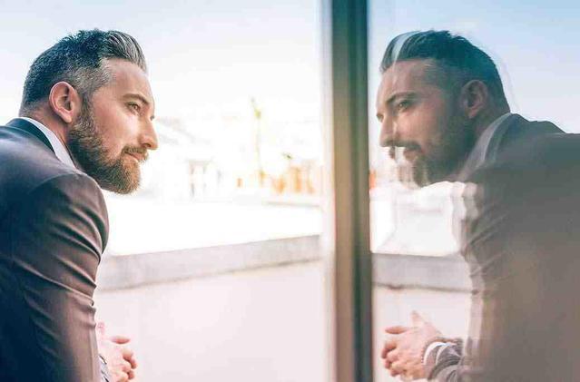 Bild eines Mannes, der seine Spiegelung im Fenster betrachtet