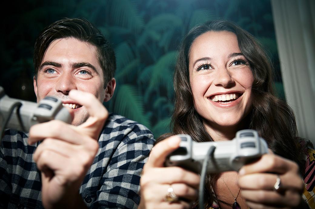 Zwei Erwachsene die ein Videospiel auf einer Konsole spielen.