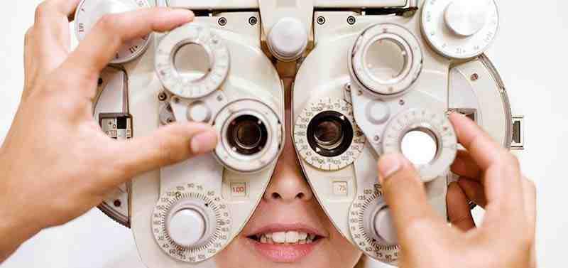 Ein Optiker justiert ein Meßgerät durch das eine junge Frau schaut