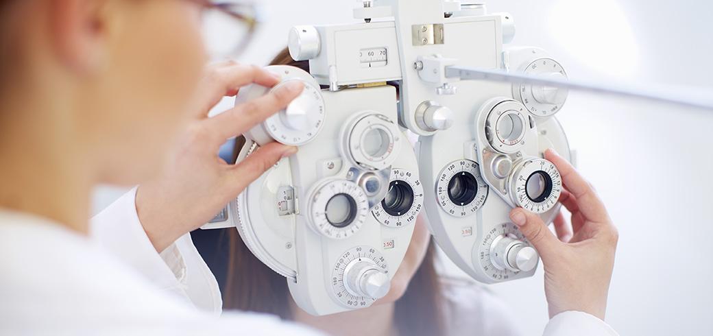 Bild eines Optikers, welcher das Sehtestgerät einstellt.
